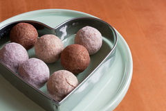 Chocolate truffles. Closeup of chocolate truffles in a heart shaped tin frame on a dessert stand Stock Image