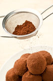 Chocolate truffles. Cocoa powder being sprinkled from a sieve over bowl of chocolate truffles Royalty Free Stock Images