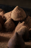 Chocolate truffles with cocoa powder. Homemade dark chocolate truffles in spilled cocoa powder close-up. Low light stock photos