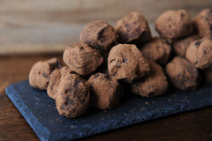 Chocolate truffles in cocoa sprinkled. On the slate board on wooden background. Close-up, texture stock photos