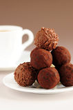 Chocolate truffles and coffee. Gourmet chocolate truffles on a plate with a cup of coffee stock photo