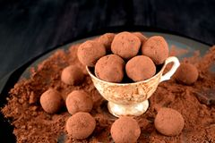 Chocolate truffles covered with cacao. In a ceramic cup royalty free stock photos