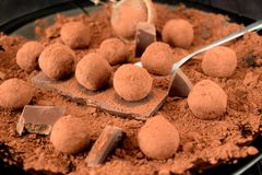 Chocolate truffles covered with cacao powder. On a black plate royalty free stock photography