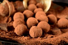 Chocolate truffles. Covered with cacao powder on a black plate royalty free stock photography