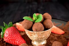 Chocolate truffles covered with cacao powder. In a brown cup surrounded by strawberries stock photos