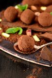 Chocolate truffles covered with cacao powder. Pistachio nuts, chocolate and mint on a dark wooden board royalty free stock images