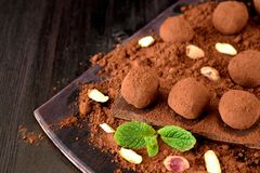 Chocolate truffles covered with cacao powder. Pistachio nuts, chocolate and mint on a dark wooden board stock photos