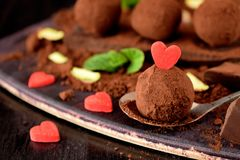 Chocolate truffles covered with cacao powder. And red sugar hearts are scattered around stock image