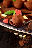 Chocolate truffles covered with cacao powder. And red sugar hearts are scattered around royalty free stock photography