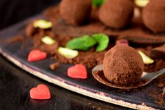 Chocolate truffles covered with cacao powder. And red sugar hearts are scattered around royalty free stock photo