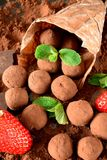 Chocolate truffles covered with cacao powder. And strawberries are falling out of the paper package stock photography