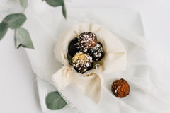 Chocolate Truffles Decorated with Gold Glitter and Coconut Flakes in Small Pot on White Plate Royalty Free Stock Photography