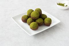 Chocolate Truffles dusted with Green Matcha Powder. Homemade chocolate truffles dusted with green matcha powder arranged on a white plate Stock Photography