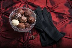 Chocolate Truffles on a red background with black gloves and ring. stock images
