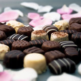 Chocolate truffles and rose petals. With differential focus royalty free stock photo
