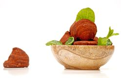 Chocolate truffles in a round bowl. Chocolate truffles and mint leaves in a round marble bowl, isolated on white background stock image