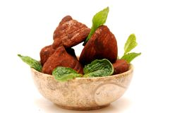 Chocolate truffles in a round bowl. Chocolate truffles and mint leaves in a round marble bowl, isolated on white background royalty free stock image