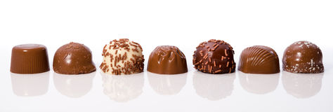 Chocolate truffles. Row of chocolate truffles on white background with reflections royalty free stock photos