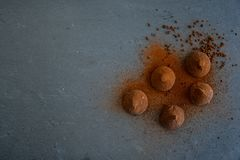 Cocoa truffles. Chocolate truffles shot from above on on black slate. Free text space stock photo