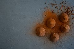 Cocoa truffles. Chocolate truffles shot from above on on black slate. Free text space royalty free stock images