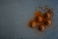 Cocoa truffles. Chocolate truffles shot from above on on black slate. Free text space stock image