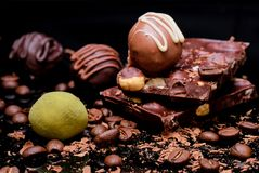 Chocolate truffles, slices of chocolate with hazelnats, and coffee beans royalty free stock photography