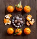 Chocolate truffles and tangerins Stock Photos