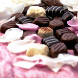 Chocolate truffles with white and pink rose petals Stock Photo