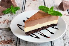 Chocolate vanilla cheesecake against rustic white wood Royalty Free Stock Images