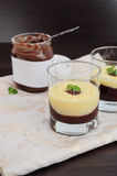Chocolate and vanilla cream. Served in glasses, jar of chocolate spread in the background Stock Photo