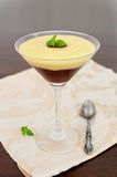 Chocolate and vanilla cream. Served in tall glass, decorated with mint leaf Stock Image