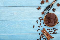 Chocolate, vanilla sticks, cinnamon, coffee beans on blue wooden background with copy space for your text. Top view Stock Photo