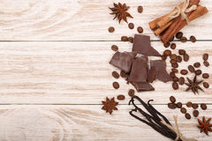 Chocolate, vanilla sticks, cinnamon, coffee beans on white wooden background with copy space for your text. Top view Royalty Free Stock Photography