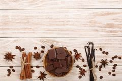 Chocolate, vanilla sticks, cinnamon, coffee beans on white wooden background with copy space for your text. Top view Royalty Free Stock Photo