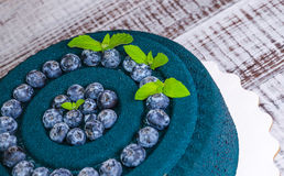 Chocolate velour cake with blueberries and basil leaves Stock Images