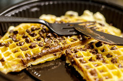 Chocolate Waffle. Chocolate covered waffle in a plastic to-go plate, with plastic fork and knife on top. A slice of waffle is missing from the plate Royalty Free Stock Image