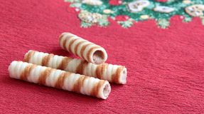 Chocolate waffle rolls on christmas mat. Crispy chocolate waffle rolls on christmas mat Stock Photography