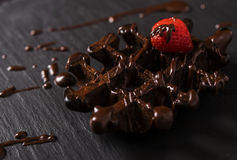 Chocolate waffles with chocolate sauce. With strawberries on top of the shale plate Stock Photo