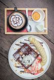 Chocolate waffles with vanilla ice cream, banana, whipped cream. And strawberry syrup. chocolate waffles in cozy outdoor cafe.selective focus, vintage effect stock images