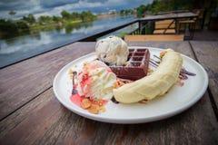 Chocolate waffles with vanilla ice cream, banana, whipped cream Stock Photo
