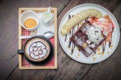 Chocolate waffles with vanilla ice cream, banana, whipped cream. And strawberry syrup. chocolate waffles in cozy outdoor cafe.selective focus, vintage effect royalty free stock photo