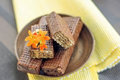 Chocolate waffles  on a yellow napkin with orange flowers. Top view. Chocolate waffles on a yellow napkin with orange flowers. Close-up. Horizontal. Top view royalty free stock photo