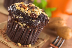 Chocolate-Walnut Muffin. With coffee cup in the back (Selective Focus, Focus on the front edge of the muffin Stock Photo