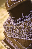 Chocolate Wedding Cake. Close up of chocolate wedding cake with purple frosting accents and patterns Royalty Free Stock Image