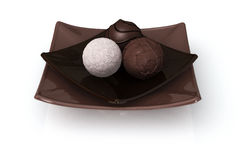 Chocolate on White. Three chocolate truffles on a plate isolated over a white background stock illustration