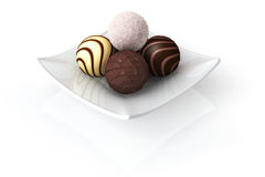 Chocolate on White. Chocolate truffles on a plate isolated over a white background royalty free stock image
