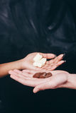 Chocolate in white and black hands, color contrast. Chocolate White Black Hand Contrast Closeup Interracial Color Sweet Seduction Love Mix Temptation Concept stock photo