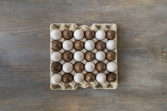 Chocolate and white boiled eggs in a recycled paper tray Royalty Free Stock Photography
