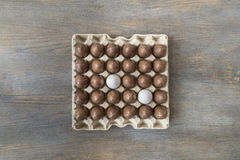 Chocolate and white boiled eggs in a recycled paper tray Stock Images