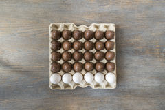 Chocolate and white boiled eggs in a recycled paper tray Royalty Free Stock Images